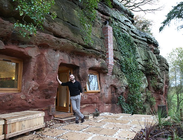 Proud Angelo stands on his cave home's patio