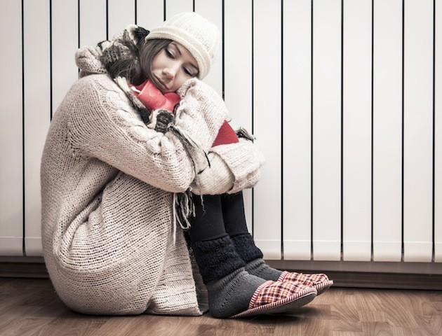 Girl wrapped up in warm clothes clutching a hot water bottle sitting next to a radiator