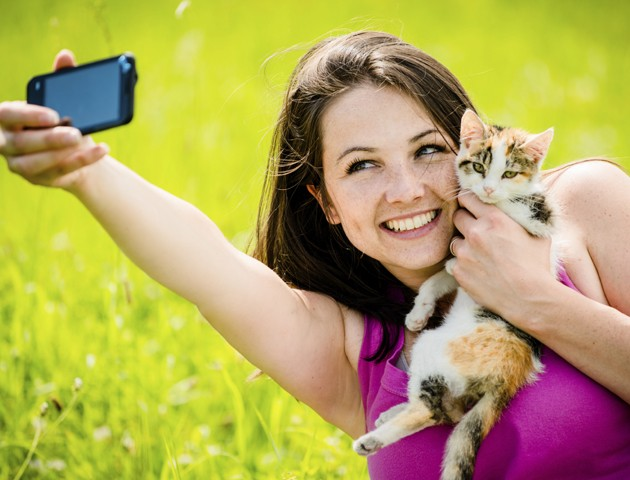 image of woman with cat taking a selfie
