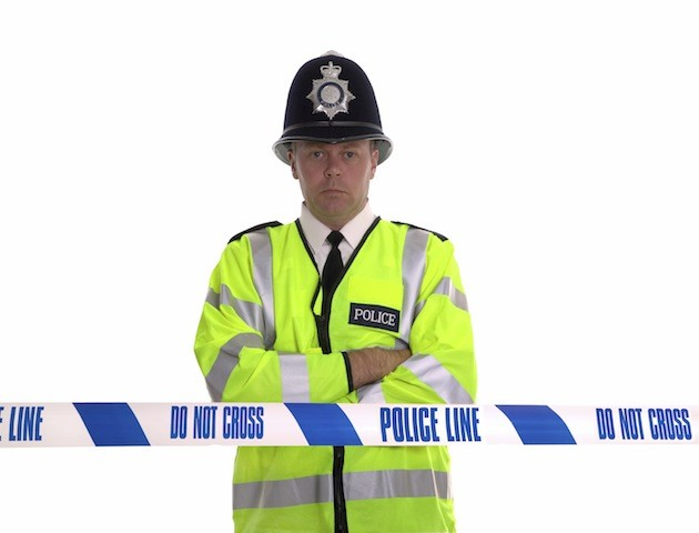 UK policeman standing behind Police Line tape
