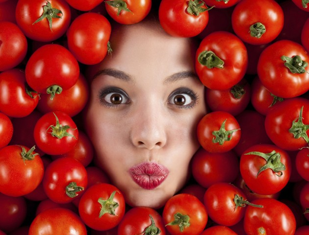image of womans face surrounded by tomatoes