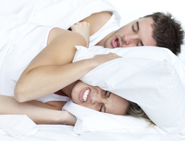 image of woman hiding under a pillow from man snoring