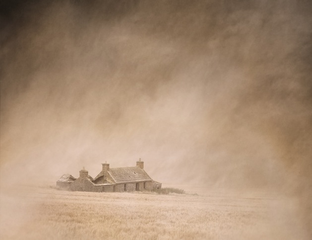 Derelict farm cottage in a vast, dusty, windswept cornfield captured using long exposure, bokeh and other effects with some areas blurred to create a surreal and dreamlike effect.