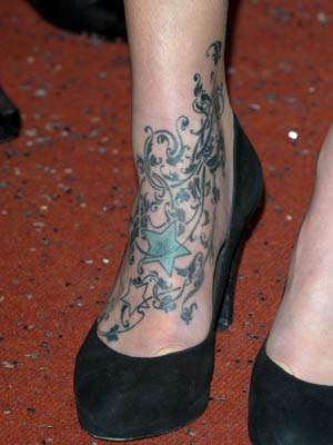 Whose foot is covered in leaf-like tats?