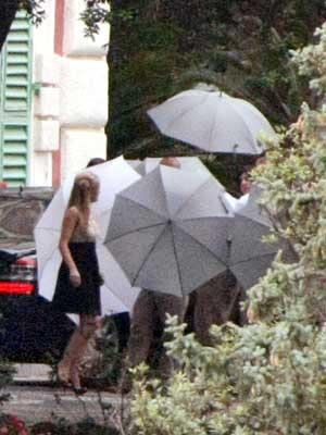 Umbrellas shield the blushing bride