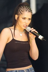 Cheryl takes inspiration from sporty spice and wears the tom-boy look with jeans and a black top. The look is completed by the hair braids and a slicked back ponytail!