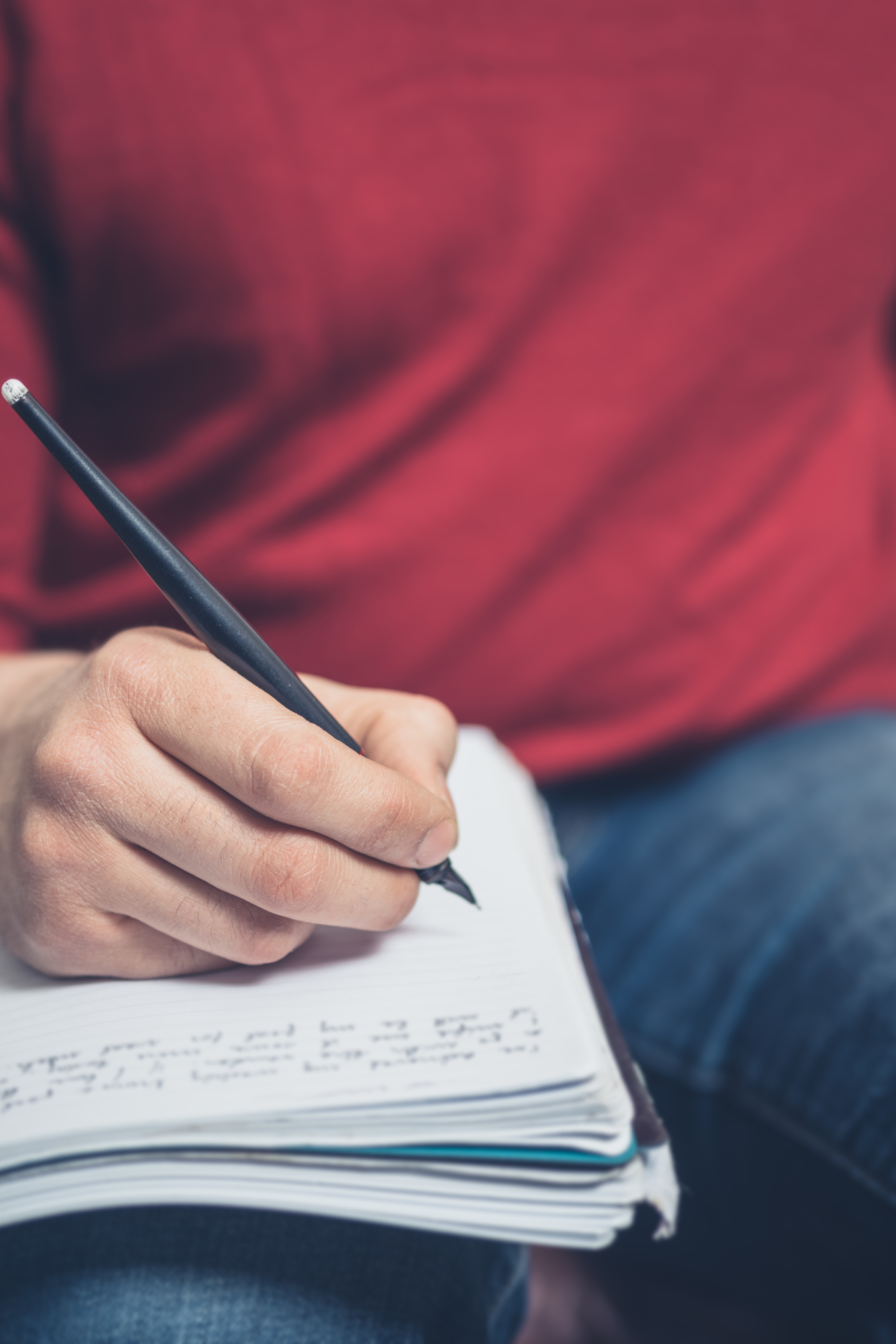 Close up on a man sitting on a sofa and writing in a notebook