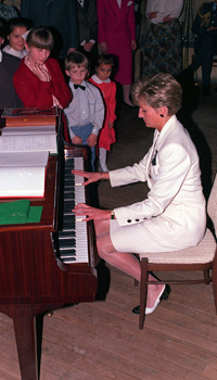 """PA NEWS PHOTO : 9/5/91 : THE PRINCESS OF WALES PLAYS PIANO TO A GROUP OF CHILDREN FROM THE SOS CHILDREN'S VILLAGES AT A RECEPTION IN PRAGUE CASTLE. HER RENDITION OF """"GREENSLEEVES"""" BROUGHT A ROUND OF APPLAUSE FROM CHILDREN AND ADULTS ALIKE."""