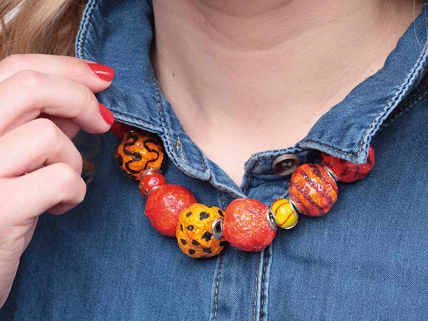 A Patterned Necklace Made From Papier Mache