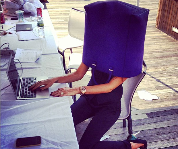 Victoria Beckham coveres her face with a purple tote bag in her New York office