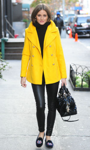 Olivia Palermo wearing a bright yellow peacoat over an all black outfit in New York