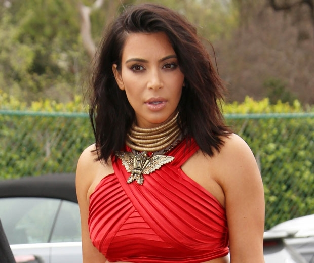 kim kardashian with short hair in a red grecian style crop top and skirt