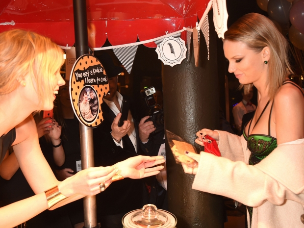 Taylor Swift and Karlie Kloss dive into the biscuit-making stall at fund fair