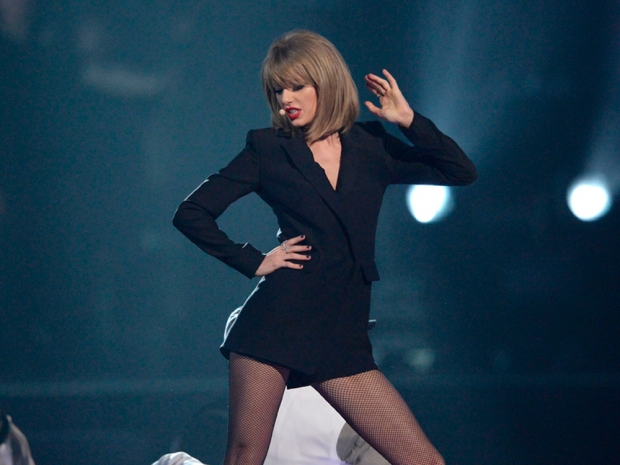 Taylor Swift performing at the brits in a black short suit and fishnet tights
