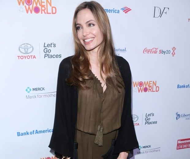 angelina jolie in a green shirt and a black cardigan smiling