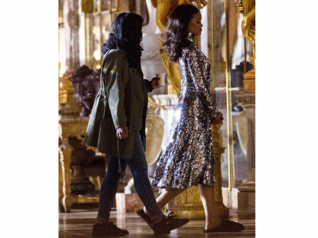 rihanna in a gold glitter coat and slippers in the Palace of Versailles