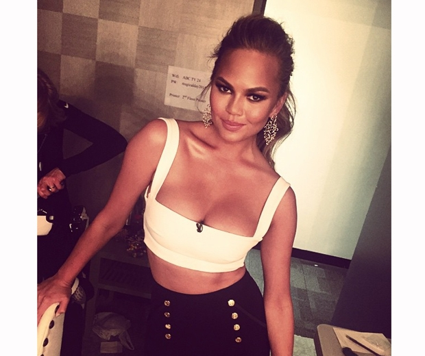 chrissy teigen in a white crop top and black skirt