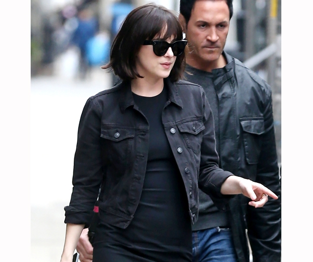 dakota johnson in black dress, black denim jacket and shades