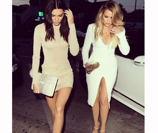 khloe kardashian in white dress and kendall jenner in nude skirt and polo neck