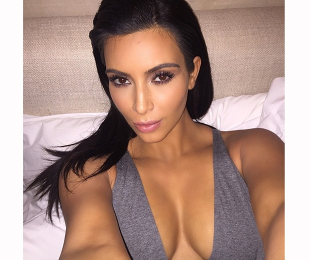 kim kardashian in plunging grey top and slicked back hair