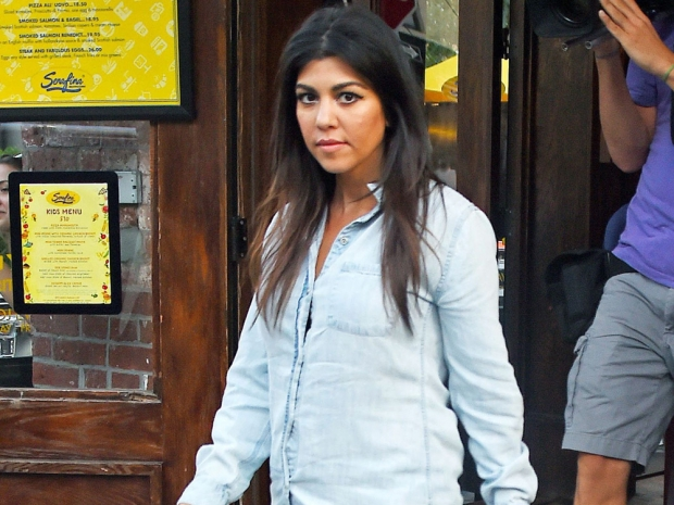 Kourtney Kardashian wearing a denim shirt while expecting her son Reign