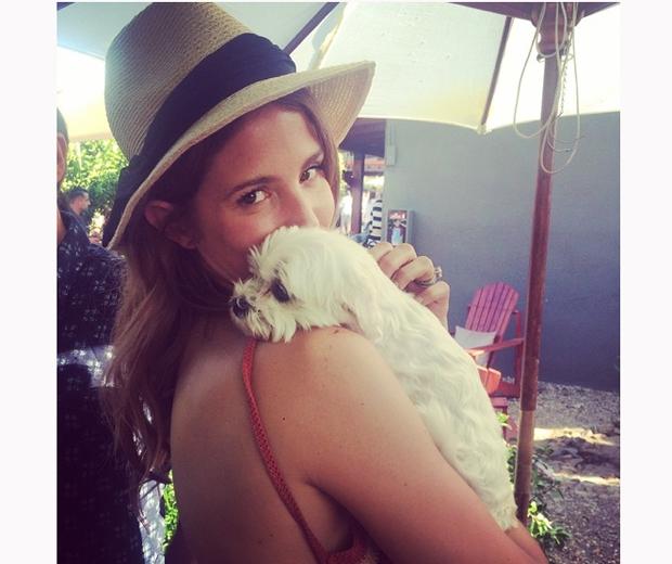 Millie Mackintosh cuddles a dog at coachella festival