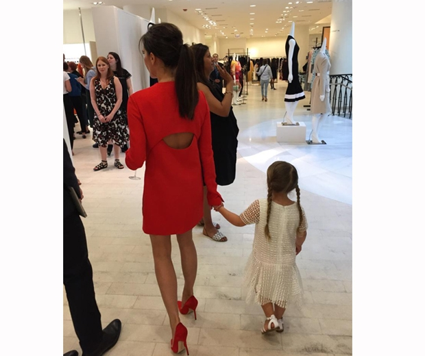 Victoria Beckham in a red dress and daughter Harper at barney's new york