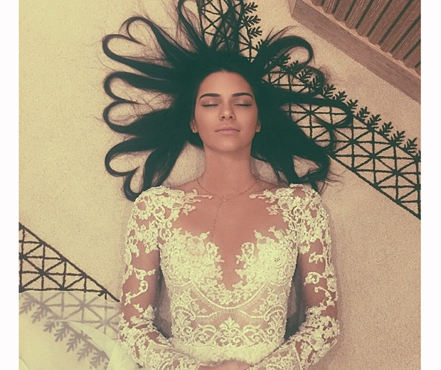 kendall jenner in white lace dress with hair forming heart shapes