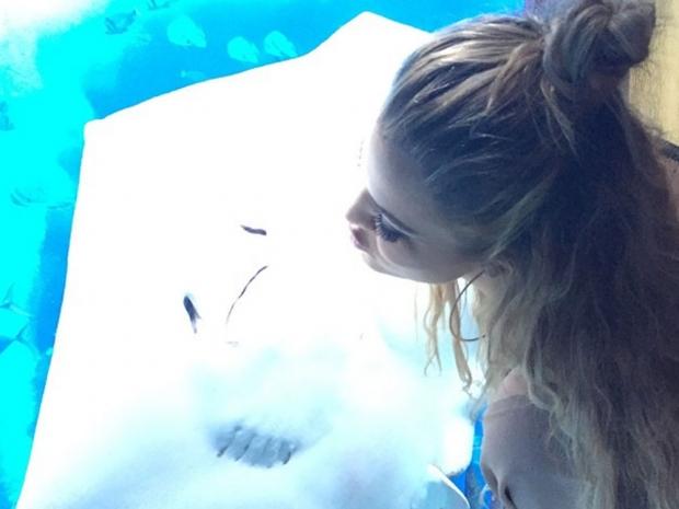 Khloe Kardashian posing by her room's aquarium in Dubai