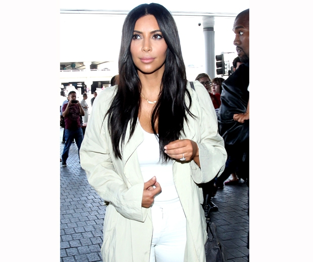 kim kardashian with long dark hairin white coat and white jeans