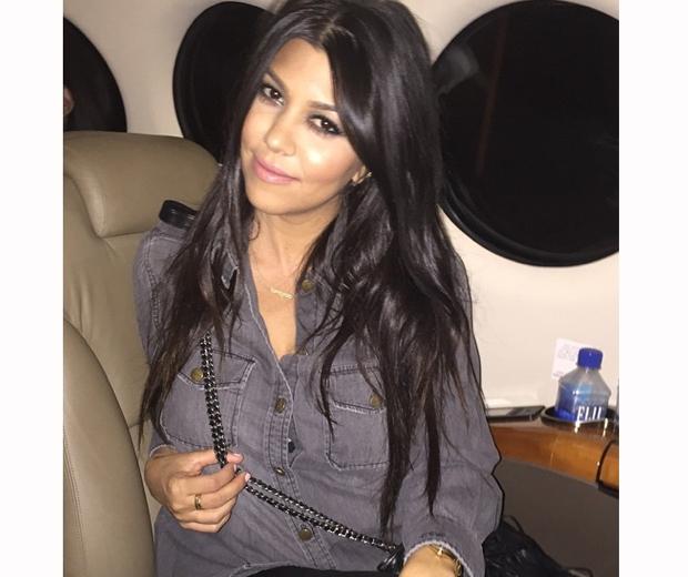 kourtney kardashian on a plane in a blue shirt