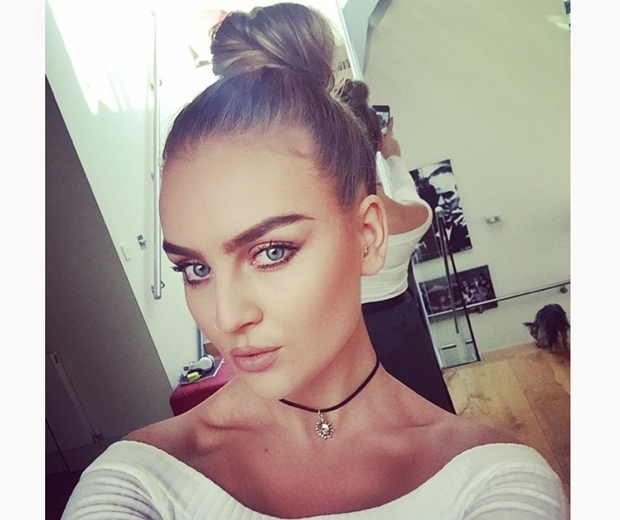 Little Mix's Perrie Edwards with topknot and dark eyebrows in a white top