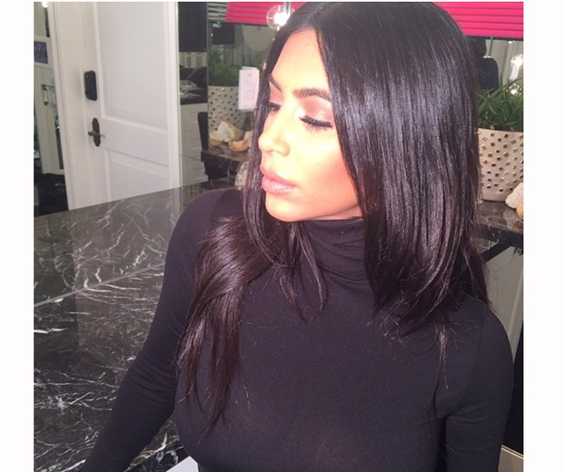 Kim Kardashian in a black rollneck with long dark hair