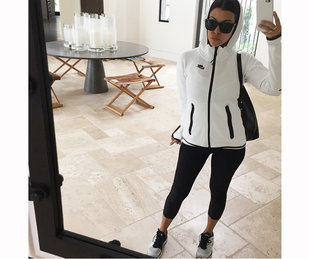 kourtney kardashian in leggings and a white zip up top