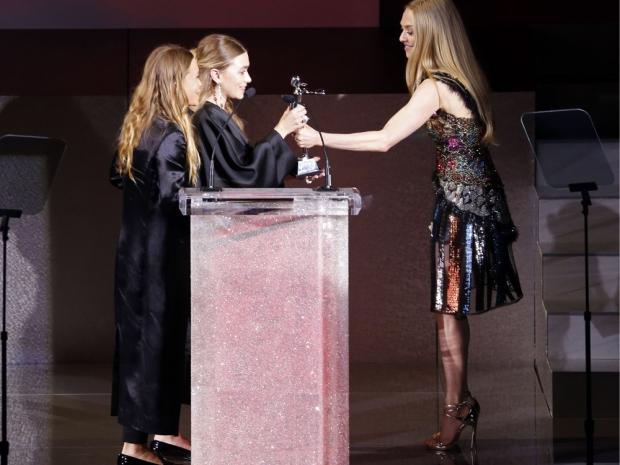Amanda Seyfriend presenting Mary-Kate and Ashley Olsen with a CFDA Award