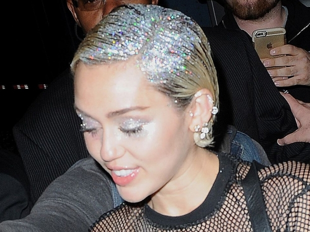 Miley Cyrus wearing hair and body glitter in New York