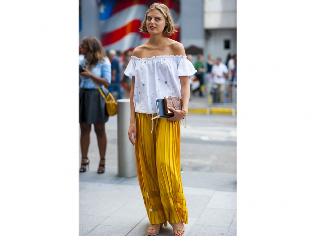 A street styler wearing palazzo pants and an off-the-shoulder top.