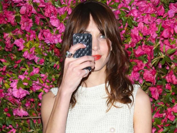 Alexa Chung holding an iPhone.