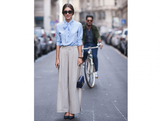 A street styler wearing palazzo pants and a chic blouse.
