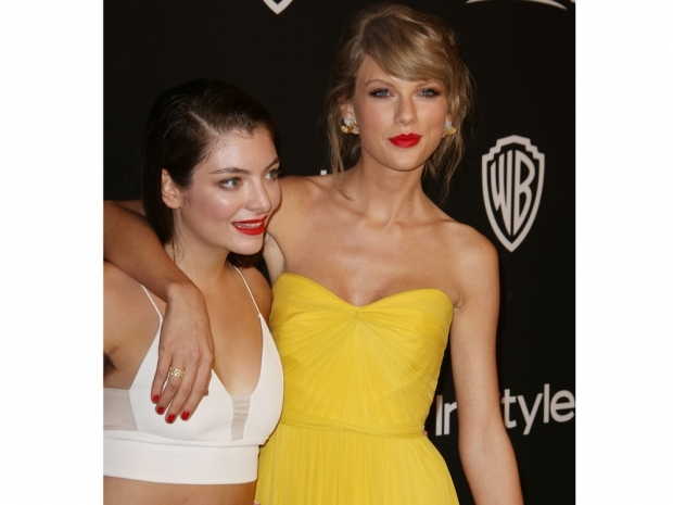 lorde and Taylor Swift in a yellow strapless dress