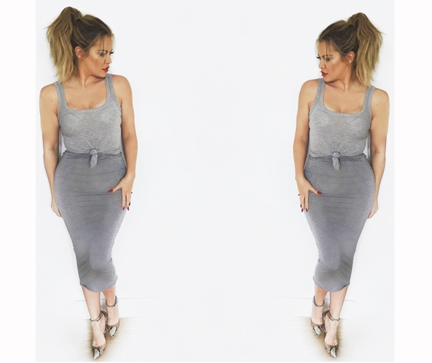 khloe kardashian in grey skirt and top with a red lip and ponytail