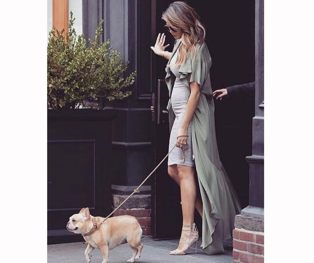 chrissy teigen in a grey dress walking her dog