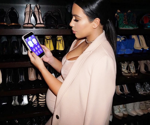 kim kardashian in a cream coat and dress looking at her phone