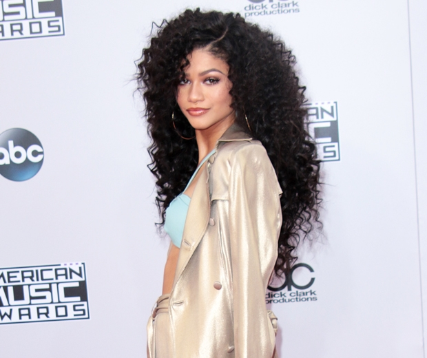 zendaya with wild curly hair and a gold jacket on