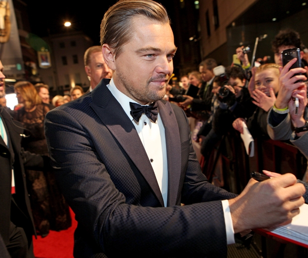 Leonardo dicaprio signing autographs for fans before the BAFTAs ceremony...