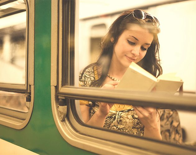 edityoung-woman-is-reading-a-book-while-commuting-picture-id508050559