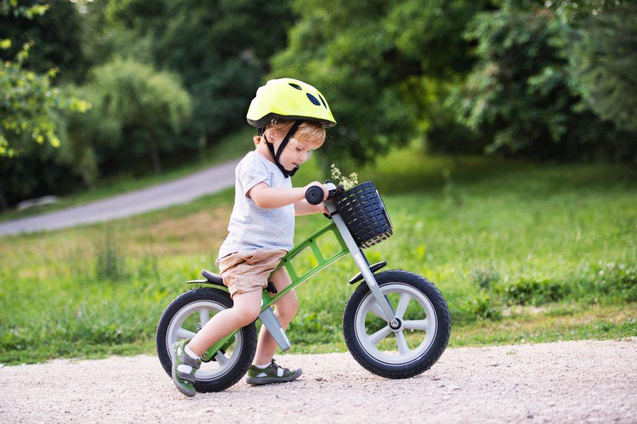 A small toddler boy riding a balance bike outdoors
