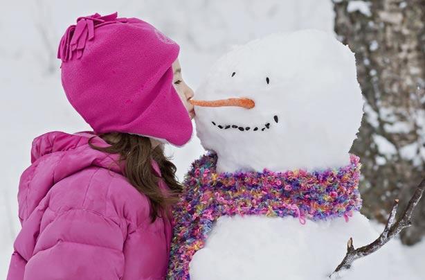 Little girl kissing a snowman