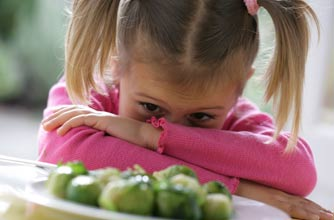 girl unhappy at plate of Brussles sprouts