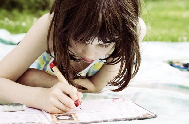 Little girl writing a letter